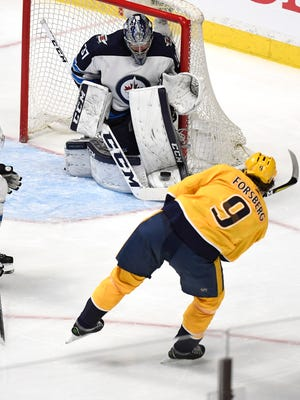 Jets goalie Connor Hellebuyck (37) makes a stop on a shot by Predators left wing Filip Forsberg (9) during the first period of Game 1 on Friday.
