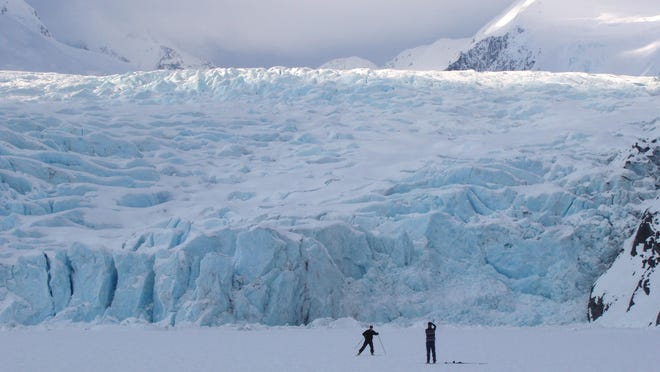 In this March 29, 2006 photo, a skier poses for a photograph on Portage Lake in front of Portage Glacier, about 50 miles south of Anchorage, Alaska. The Portage Glacier, which is a major Alaska tourist destination near Anchorage, has retreated so far it no longer can be seen from a multimillion-dollar visitors center built in 1986.