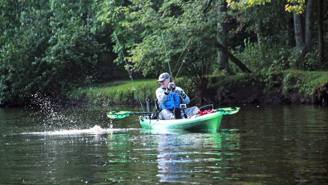 Bill Schultz of New Berln fights a smallmouth bass while fishing from a kayak on the Oconto River near Oconto, Wis.