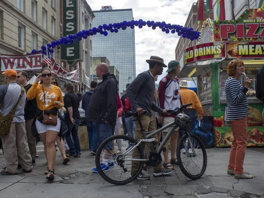 Steven Jones of Knoxville (center) rolls his bike through the crowd during the Rossini Festival on Gay Street in Knoxville on April 24, 2015. The event spread across 14 city blocks, providing food and entertainment for people of all ages.