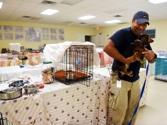 Marcel Goncalves, of Vero Beach, takes a dog out of