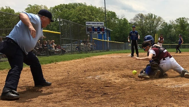 Home plate umpire Thomas Bender prepares to punch out Pearl River runner Julia Kinnally before the ball drops out of Valhalla softball catcher Emily Bisesto's mitt. Pearl River won, 4-1, at Pearl River High School on May 14, 2016.