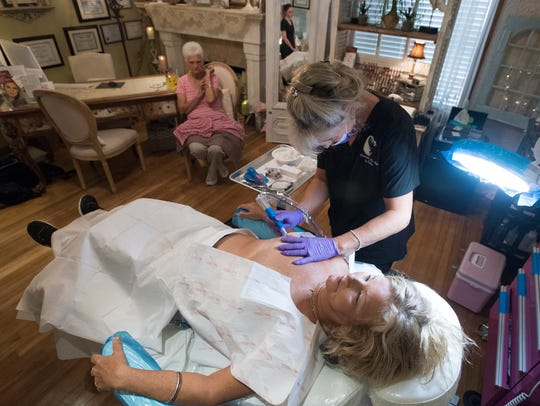 Trinkette Parker, a permanent makeup specialist, applies
