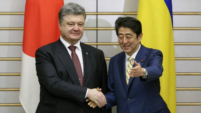 Ukrainian President Petro Poroshenko, left, shakes hands with Japanese Prime Minister Shinzo Abe in Tokyo on April 6. Poroshenko was implicated in the so-called Panama Papers scandal.