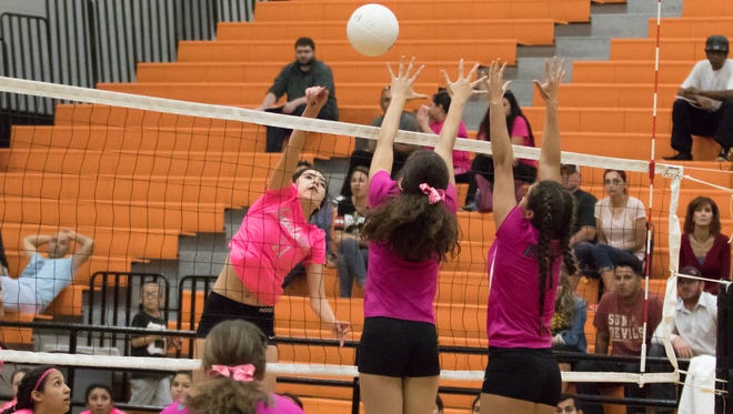 Gasdsen High School outside hitter Lauren Sifuentes hits one over Oñate blockers during District 3-6A prep volleyball Saturday at Oñate High School.