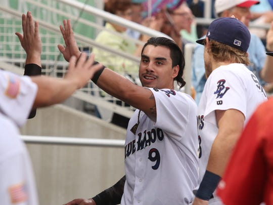 Pensacola's Sebastian Elizalde gets high-fives in the dugout after scoring on a soft hit to third base by Zach Vincej Thursday night at Blue Wahoos Stadium.