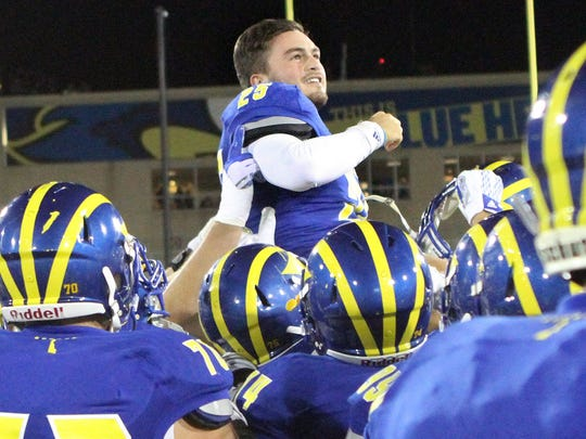 Delaware kicker Frank Raggo is hoisted by his teammates after kicking a 29-yard field goal as time expired to give the Blue Hens a 24-23 win against William and Mary at Delaware Stadium Saturday.
