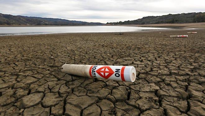 A warning buoy sits on the dry, cracked bed of Lake Mendocino near Ukiah, Calif.