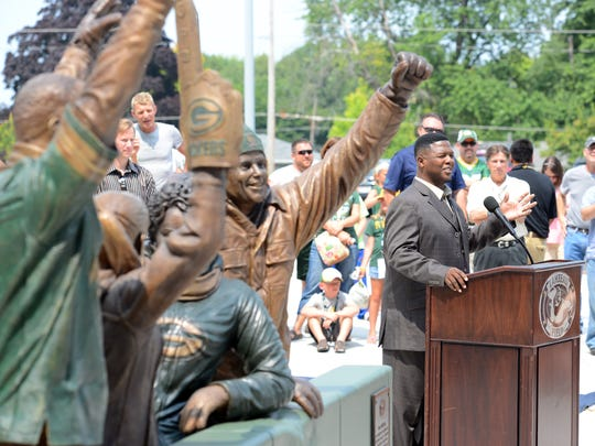 LeRoy Butler, right, credited with originating the Lambeau Leap, talks about the fans' love for the Packers during Friday's unveiling of the Lambeau Leap sculpture, at left, on Harlan Plaza at Lambeau Field.