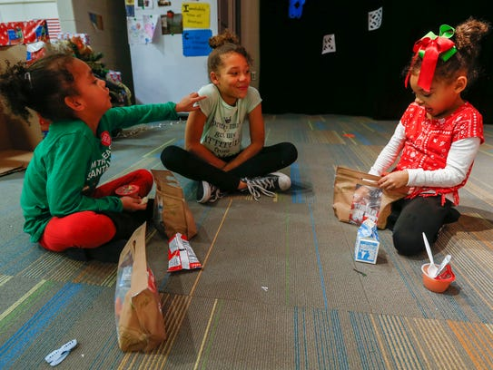 From left, Kaydence Parker, Jaida Generette and Kyleigh Parker enjoy a snack after they participated in an after-school program at Fremont Elementary School on Wednesday, Dec. 21, 2017.
