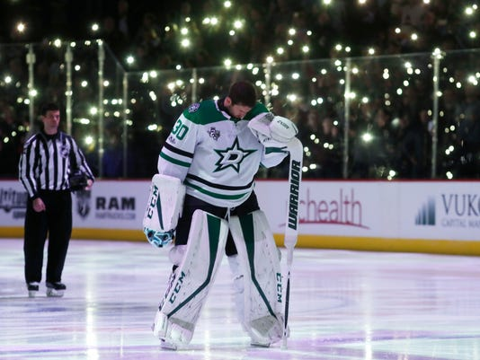 As fans use their mobile telephones to create points of light to mark Fight Cancer Month in the NHL, Dallas Stars goalie Ben Bishop bows his head during a moment of silence before facing the Colorado Avalanche in the first period of an NHL hockey game Wednesday, Nov. 22, 2017, in Denver. (AP Photo/David Zalubowski)