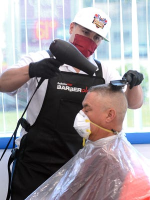 Ariel Torres gets a haircut from Luis Jimenez, both of Taftville, at the Garage Barbershop on West Main Street in Norwich Monday as Connecticut salons and barbershops are now allowed to reopen. See videos at NorwichBulletin.com