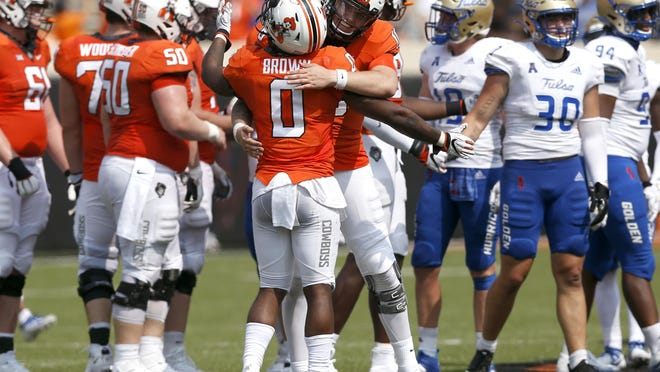 Oklahoma State's Shane Illingworth hugs teammate LD Brown after a win over Tulsa during their first game of the season at Boone Pickens Stadium in Stillwater on Saturday.