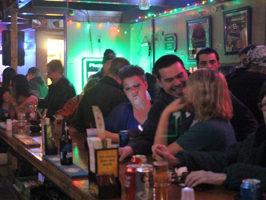 Patrons of the Someplace Else bar enjoy a drink during