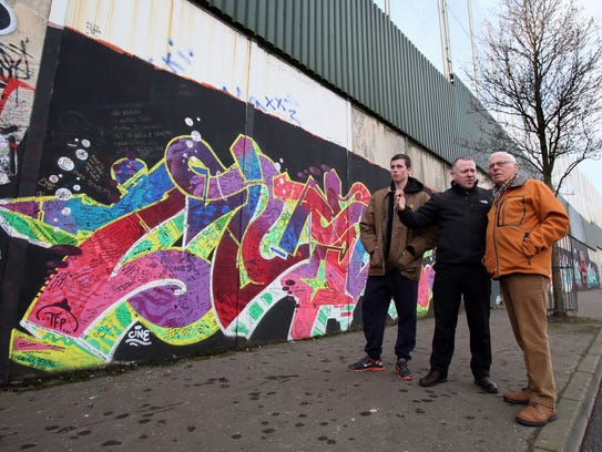 A Tour guide shows tourists a peace wall in north Belfast on Jan. 23, 2017.