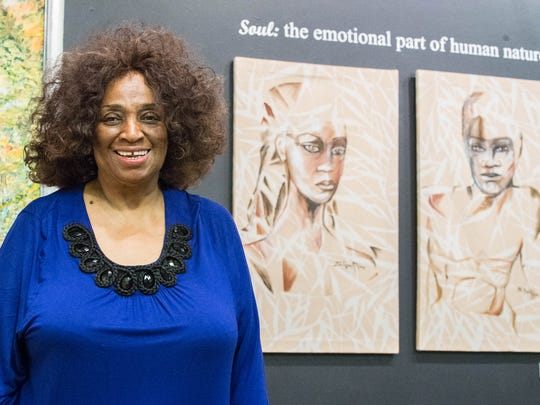 "Selena Griffin next to some of her work at the opening reception for the ""Art of Soul"" exhibit at the Art Center of Battle Creek on Sunday."