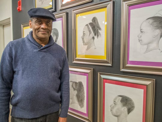"Jerome Washington from Albion stands next to some of his drawings of Battle Creek school children at the opening reception for the ""Art of Soul"" exhibit at the Art Center of Battle Creek on Sunday."