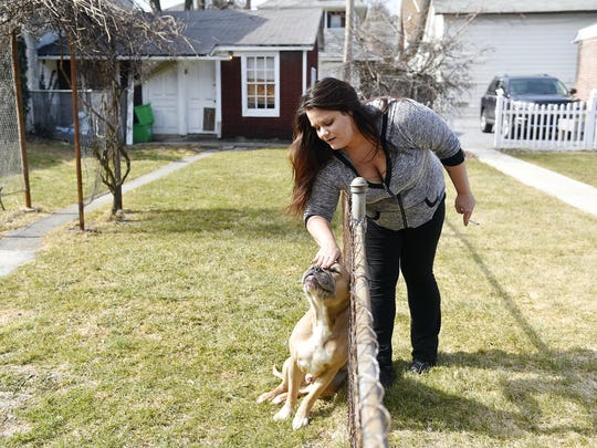 "Christina Whelan, 27, of New Jersey, pets a neighbor dog named Killer while taking a cigarette break outside the Pennsylvania Avenue house where she lives and which is operated by Choices Recovery House. Whelan, whose addictions are heroin and Xanax, said she had been to 16 different rehabilitation or treatment centers in states including New York, Florida, California and Tennessee. ""Nothing ever worked for me,"" Whelan said of her struggle to stay clean before coming to Choices. ""No matter where I went, I was with myself. It didn't matter if there were palm trees or dumpsters."""