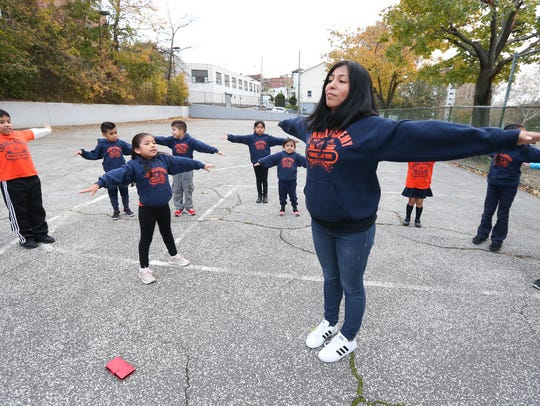 Coach Wendy Benitez, center, warms up with her runners