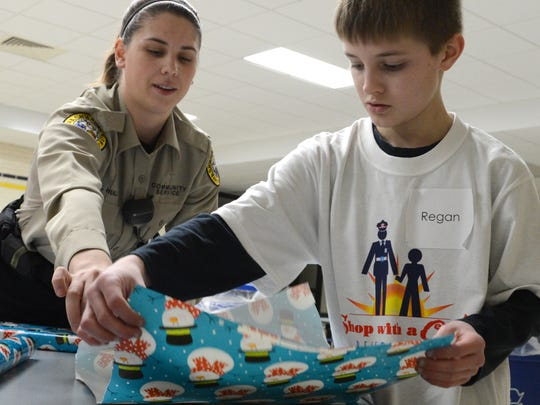 Ashley Hull of the Ashwaubenon Public Safety Department helps Regan Dresher wrap Christmas gifts Saturday as part of the annual Shop with a Cop event in Ashwaubenon.