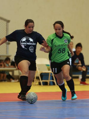 Team Mosa's Jenna Gaminde attempts to pass the ball away from Bank of Guam Lady Strykers' Alexy Dacanay in a Week 7 match of the Bud Light Women's Futsal League Sunday at the Guam Sports Complex gym. The Lady Strykers won 7-1.