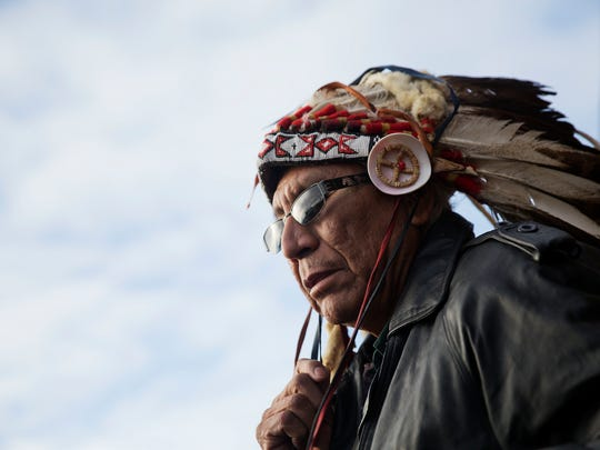 In this Dec. 4, 2016, file photo, Chief Arvol Looking Horse, a spiritual leader of the Great Sioux Nation puts on his headdress for an interfaith ceremony at the Oceti Sakowin camp where people have gathered to protest the Dakota Access oil pipeline in Cannon Ball, N.D. As cities and towns host July 4th parades and fireworks shows, some minority residents are expressing mixed feelings about the holiday used to reaffirm the country's founding based on equality and civil liberties.