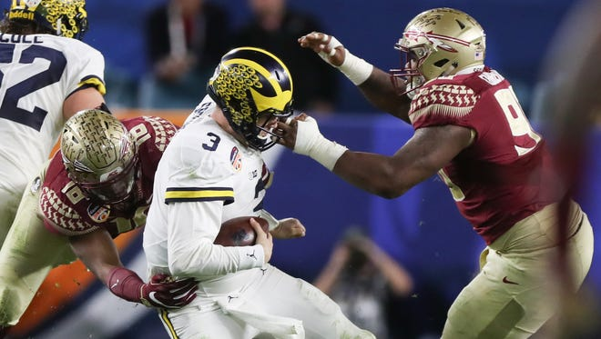 Michigan quarterback Wilton Speight draws the face mask penalty on Florida State defensive tackle Derrick Nnadi during the second half of U-M's 33-32 loss in the Orange Bowl to Florida State on Friday, Dec. 30, 2016 in Miami Gardens, Fla.
