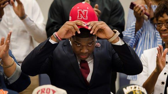 Cameron Taylor puts on a Nebraska hat as he commits