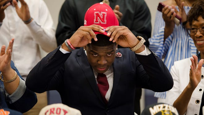 Cameron Taylor puts on a Nebraska hat as he commits to Nebraska on Wednesday, Feb. 7, 2018, in Montgomery, Ala.