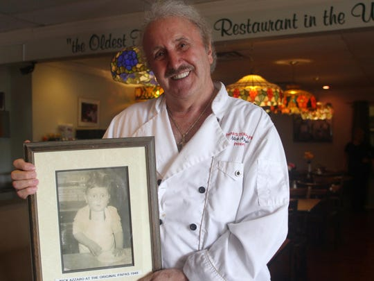 Nick Azzaro, owner of Papa's Tomato Pies in Robbinsville, holds a photo of himself making a pizza when he was 2 years old.