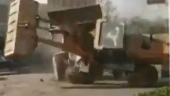 A front end loader is pushed over by another in a street