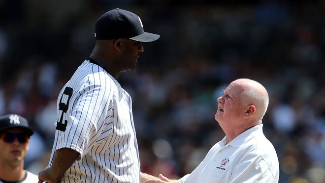 Yankees starting pitcher CC Sabathia is checked on by a team trainer before being removed from the game against the Indians during the third inning with a sore knee at Yankee Stadium.