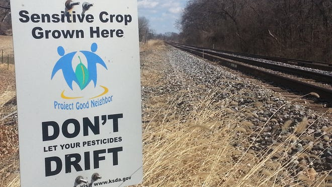 A sign put up by the Kansas State Department of Agriculture alerts nearby farmers to crops sensitive to herbicide drift.