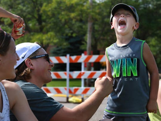 Brayson Schneider, 4, reacts as he gets his thumb pinned while thumb wrestling with older friend Karter Underwood, 17, while they watched the Punt, Pass & Kick competition during Marathon Fun Days, Saturday, September 5, 2015. At left is Underwood's girlfriend Natasha Hauke, 17.