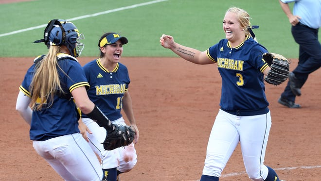 Michigan pitcher Megan Betsa, right, celebrates with catcher Aidan Falk, left, and third baseman Lindsay Montemarano after getting the last out of the game Sunday.