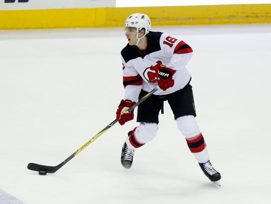 New Jersey Devils defenseman Steven Santini carries