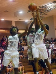 Pineville's Indiya Smith (35, left) and Daja Franklin (30, right) and Winnfield's Raina King (23, center) go after a rebound during 2015's tournament.