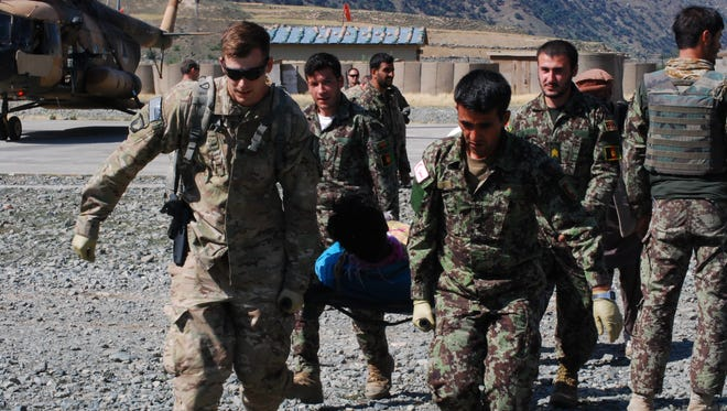 U.S. and Afghan military medical staff carry a wounded Afghan patient to a medical clinic in Nari District, Kunar Province.
