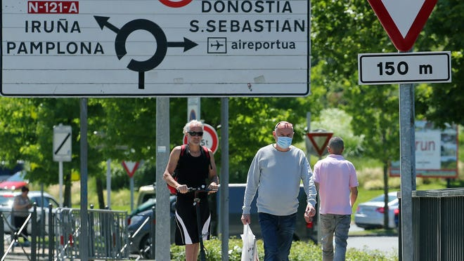 People cross the border between France and Spain at the Behobie pass, southwestern France, Sunday, June 21, 2020. Spain has opened its borders to members of the EU's Schengen Zone, including its northern neighbor of France. AP Photo/Bob Edme)
