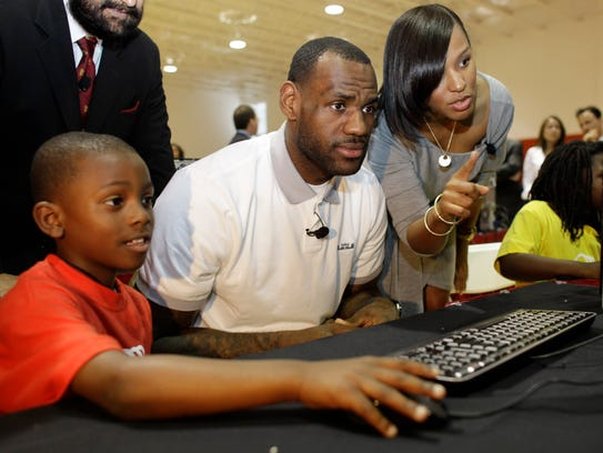 LeBron James sits with Cam'ron Lightbourne at a new