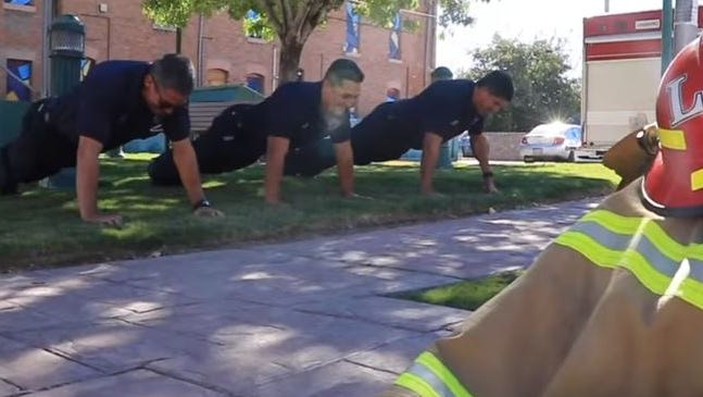 In this video screen grab, El Paso Fire Department members participate in the #22PushUpChallenge