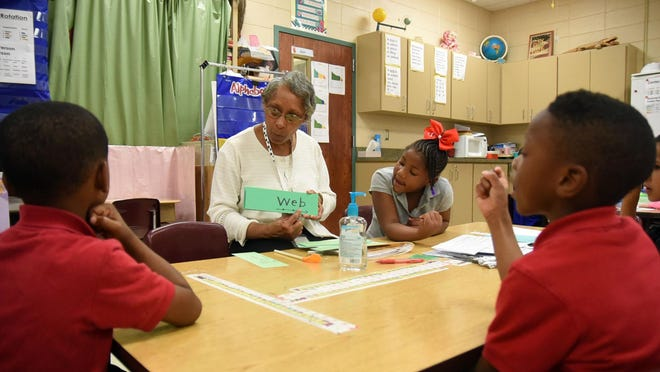 Teacher's assistant Laura Portis works with students at Lumberton Elementary School. Officials involved with organizing the consolidation of the Lumberton Public School District met Tuesday at William Carey University.