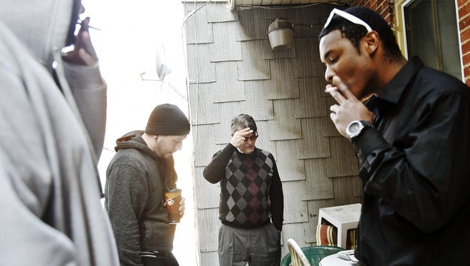 Dave Dunkel, owner of Sees-the-Day, center, shares a cigarette break with, from left, Zachary Moser, 21, of Montgomery County, Pa.; Nathan Embry, 27, of Lancaster; and Roman Fissel, 22, of Manchester Township, all of whom live in a Sees-the-Day recovery house on Linden Avenue. York is home to about 80 recovery homes that house drug and alcohol addicts who are trying to get and stay sober. The houses, which are not designed as treatment programs, are not subject to state or county regulations.