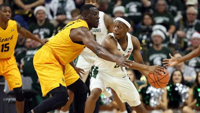 Michigan State guard Cassius Winston (5) is defended by Long Beach State forward Temidayo Yussuf (4) during the first half on Thursday, Dec. 21, 2017, at Breslin Center.