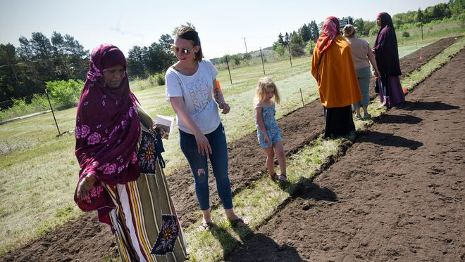 Kendra Roehl and her daughter Eleanor volunteer to help people at a community garden for area refugees Saturday, May 26, at Jubilee Church in St. Cloud.