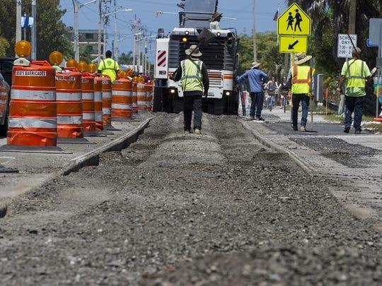 Construction employees work along Estero Boulevard in Fort Myers Beach near School Street.