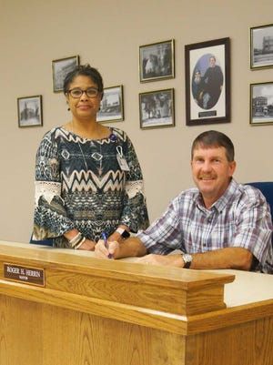 Sabrina Young, South Mississippi State Hospital director, looks on as Purvis Mayor Roger Herrin signs a proclamation declaring May Mental Health Month in Purvis.