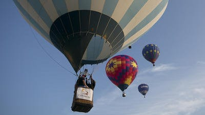 John Ross of Appleton, right, and Kevin Pelky, left, of Appleton float into the sky with other hot air balloons during the morning launch at Balloon and Rib Fest at the Wausau Downtown Airport, Saturday, July 11, 2015. Ross is the pilot for FUNtastic Ballooning based in Appleton.