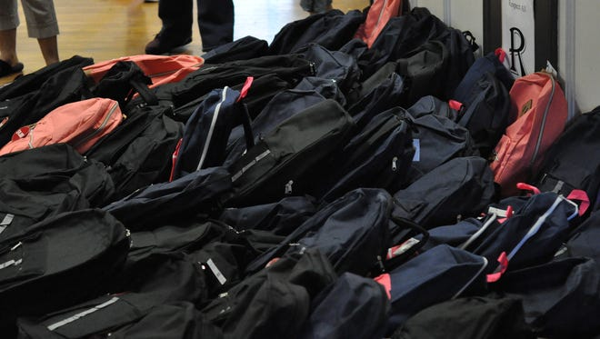 Local elementary teachers stuffed at least 100 backpacks with school supplies on Thursday. They will be given to children during a community event set for Saturday.