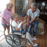Alma Watts of McLaurin carries her IV bag on a coat hanger on Sept. 6, 2005, as Sandy and Dan Lester assist Watts into their home, which served as a clinic in McLaurin.